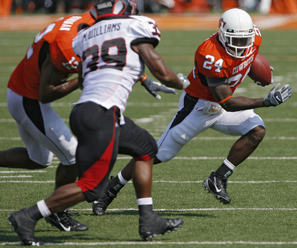 Oklahoma State\'s Kendall Hunter (24) looks for running room past Texas Tech\'s Marion Williams (39) during the first half of the college football game between the Oklahoma State University Cowboys (OSU) and the Texas Tech University Red Raiders (TTU) at Boone Pickens Stadium on Saturday, Sept. 22, 2007, in Stillwater, Okla. By MATT STRASEN, The Oklahoman
