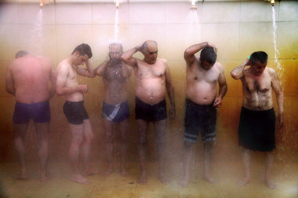 Photo - In this Sept. 11, 2013 photo, Iranian men shower at a hot mineral pool, in the northwestern town of Sarein, Iran. The steamy waters emanating from the depths of the earth are rich in sulfur, calcium, lithium and other minerals, and are believed to offer relief to patients suffering from joint pain and some skin diseases. (AP Photo/Ebrahim Noroozi)