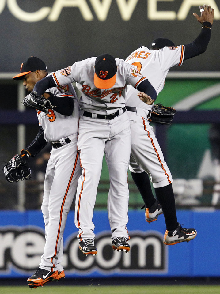 Baltimore Orioles left fielder Endy Chavez, left, celebrates with center fielder Nick Markakis, center, and Adam Jones, right, after shutting out the Yankees 5-0 in a baseball game at Yankee Stadium in New York, Wednesday, May 2, 2012. (AP Photo/Kathy Willens)
