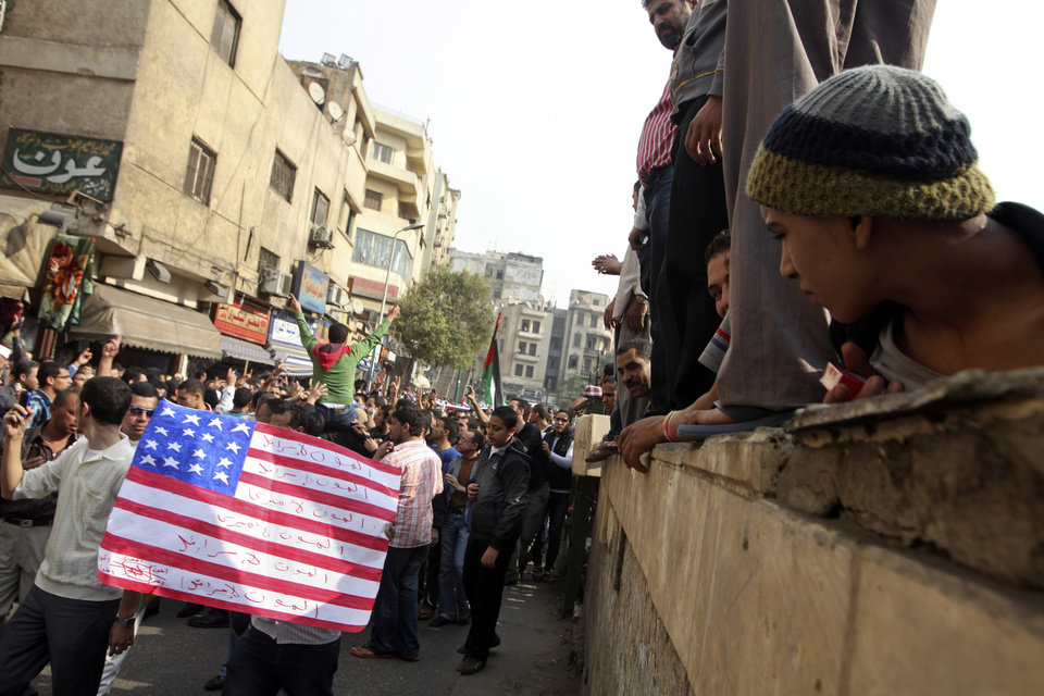 Protesters chant slogans and carry a desecrated representation of an American flag during demonstrations against the Israeli invasion of Gaza, while marching through the streets towards Tahrir square after Friday prayers in Cairo, Egypt, Friday, Nov.16, 2012. In his Friday sermon at Al-Azhar mosque, influential cleric Sheikh Yusuf al-Qaradawi, not shown, said the Islamic world would not be silent in the face of Israel\'s military operation in Gaza. Arabic writing reads,