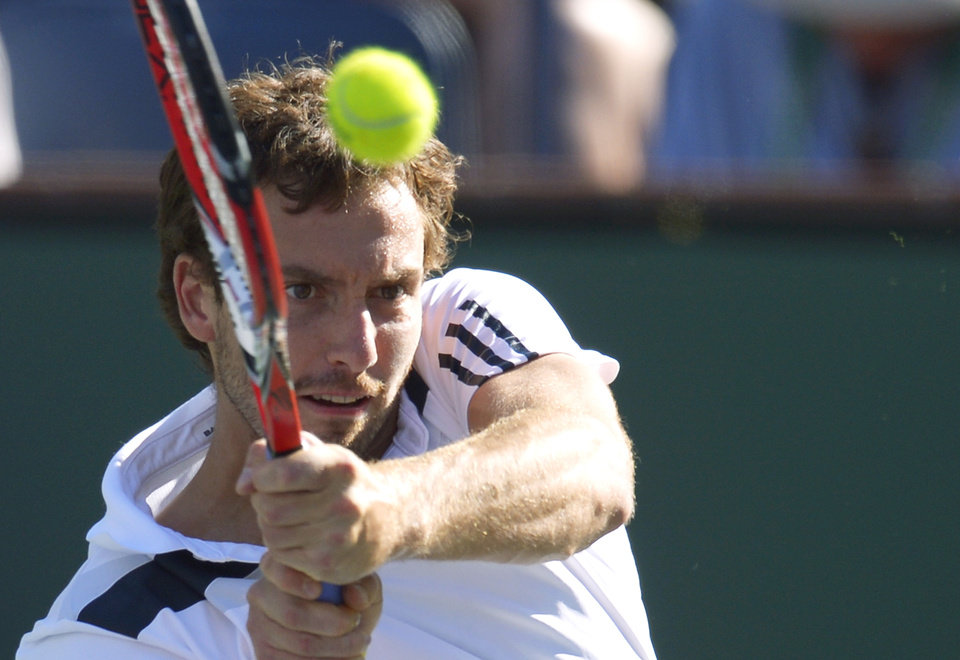 Photo - Ernests Gulbis, of Latvia, hits to John Isner during their quarterfinal match at the BNP Paribas Open tennis tournament on Friday, March 14, 2014, in Indian Wells, Calif. (AP Photo/Mark J. Terrill)