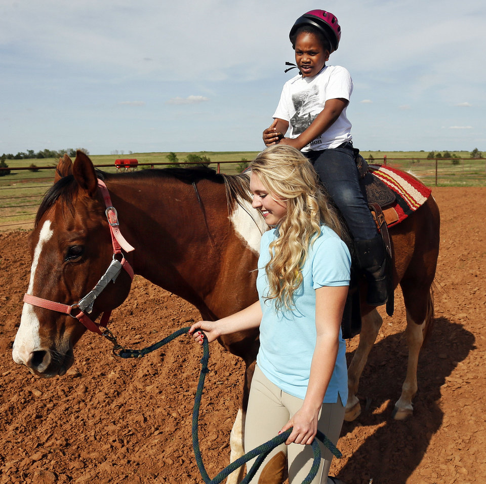 Photo - Molly Remondino, 17, leads a horse with rider Izzy Washington, 6, at the Peppers Ranch foster care community near Guthrie. Photo by Nate Billings, The Oklahoman   NATE BILLINGS