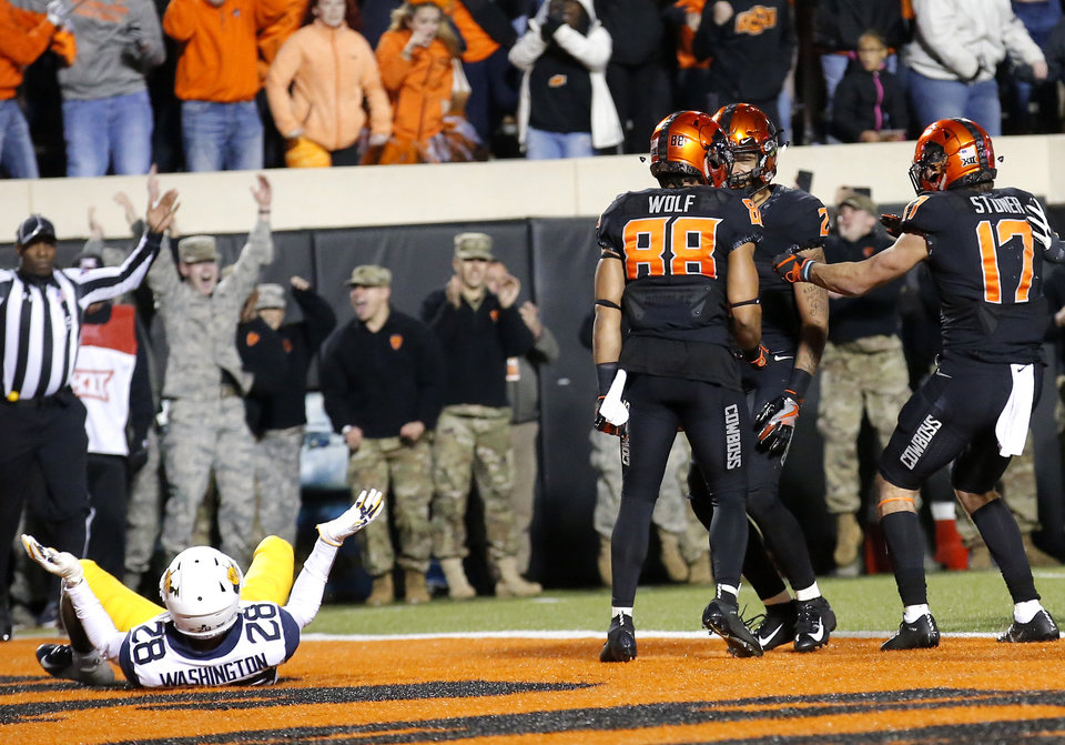 Photo -  Oklahoma State receiver Tylan Wallace has left plenty of defenders wondering how he worked his magic this season. Last week, it was West Virginia's Keith Washington, left, who got beat, then carried into the end zone on Wallace's game-winning touchdown.  [PHOTO BY SARAH PHIPPS, THE OKLAHOMAN]