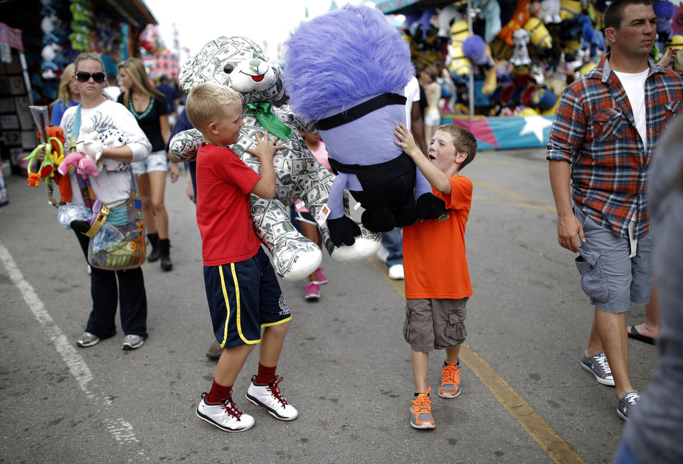 Photo - Chase Lashley, left, and Hunter Hollingsworth play their prizes as they walk through the games area at the Oklahoma State Fair in Oklahoma City, Sunday, Sept. 15, 2013. Photo by Sarah Phipps, The Oklahoman
