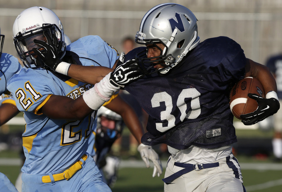 Photo - Edmond North's Richard McCauley (30) runs a ball past Putnam City West's Kerrick Myrks (21) during a scrimmage at Putnam City West High School in Bethany, Thursday, Aug. 21, 2014.  Photo by Garett Fisbeck, For The Oklahoman