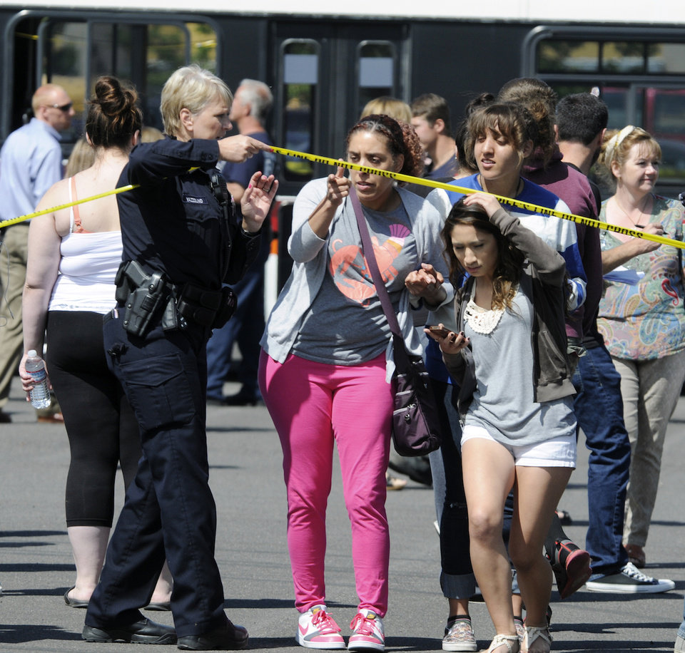 Photo - A police officer lifts up police tape as students are arrive by bus to meet their parents and/or family at the Fred Meyer grocery store parking lot in Wood Village, Ore., after a shooting at Reynolds High School Tuesday, June 10, 2014, in nearby Troutdale. A gunman killed a student at the high school east of Portland Tuesday and the shooter is also dead, police said. (AP Photo/Greg Wahl-Stephens)