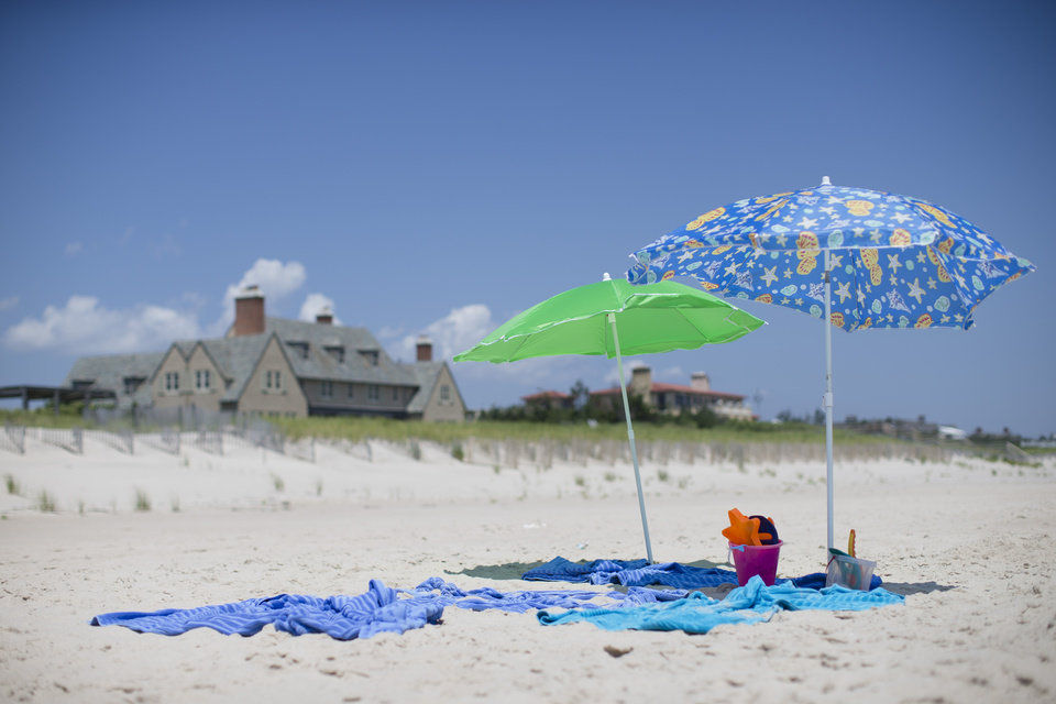 Photo - In this photo taken on Friday, July 11, 2014, beach umbrellas stand unattended outside a private residence in Southampton, N.Y. Studies show the gap separating the rich from the working poor has been ever-widening in recent years and few places provide that evidence as starkly as Long Island's Hamptons. (AP Photo/John Minchillo)