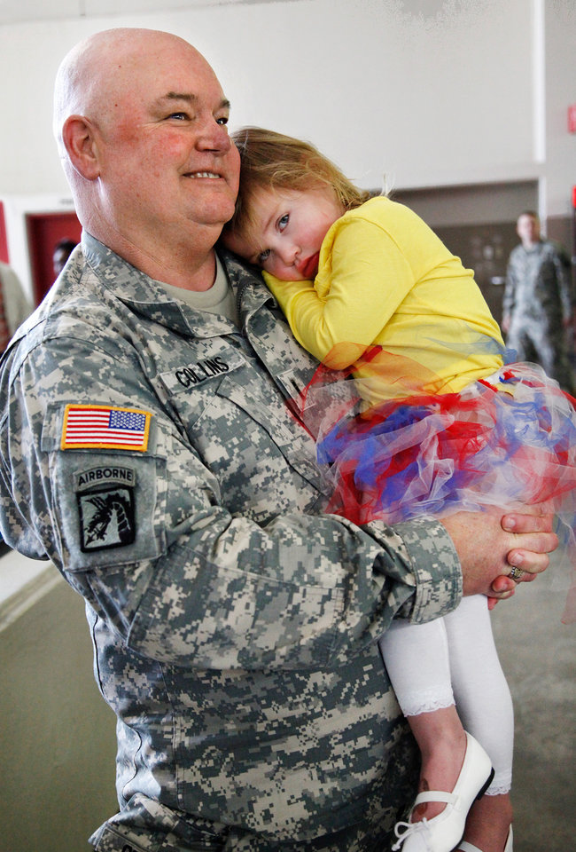 MILITARY DEPLOYMENT: Chief Warrant Officer 3 Danny Collins of Purcell holds one of his seven grandchildren after the 45th Infantry Brigade Combat Team Deployment Ceremony in downtown Oklahoma City, Wednesday, Feb. 16, 2011. Paige Collins, 3, of Davis, OK, lays her head against her grandfather's uniform. The girl's father was serving in Iraq when she was born. Four months after he returned home from duty, he was killed in a motorcycle crash.  This will be Collins' third deployment in the last 20 years. Collins said that at one point, he and three sons were serving in the military. One of his sons is deploying with the Guard group today. Photo by Jim Beckel, The Oklahoman,
