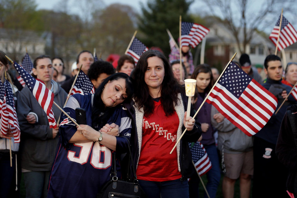 People gather on a field during a vigil for the victims of the Boston Marathon bombing, Saturday, April 20, 2013, in Watertown, Mass. Suspected bomber Dzhokhar Tsarnaev is hospitalized in serious condition with unspecified injuries after he was captured in an all day manhunt the day before. (AP Photo/Julio Cortez) ORG XMIT: MAJC125