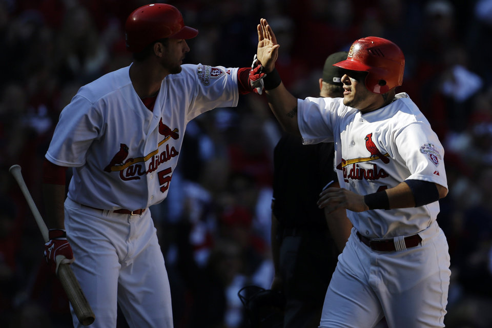 St. Louis Cardinals' Yadier Molina, right, is congratulated by Adam Wainwright after scoring on a wild pitch by Washington Nationals starter Gio Gonzalez during the second inning in Game 1 of baseball's National League division series, Sunday, Oct. 7, 2012, in St. Louis. (AP Photo/Jeff Roberson)