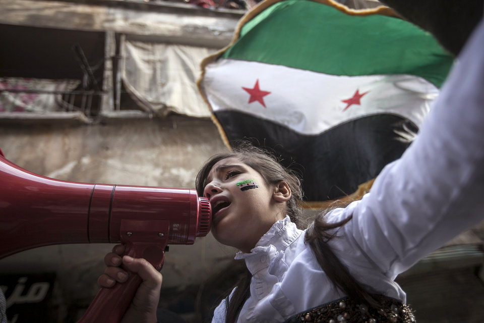 Photo - In this Friday, Nov. 30, 2012 photo, a Syrian girl chants slogans during a demonstration after Friday prayers in the Bustan Al-Qasr district of Aleppo, Syria. After months of fighting, thousands of residents have returned to the city as they attempt to return to their daily lives while heavy fighting is still taking place along the front lines in the city. Public demonstrations have unfolded after several weeks of silence as residents demand an end to the violence in Aleppo. (AP Photo/Narciso Contreras)