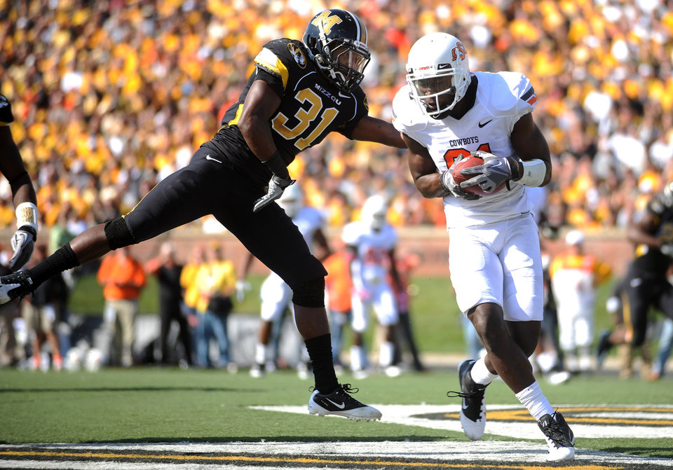Photo - Oklahoma State wide receiver Justin Blackmon, right, catches an 8-yard touchdown pass as Missouri defensive back E.J. Gaines defends during the first half of an NCAA college football game, Saturday, Oct. 22, 2011, in Columbia, Mo. (AP Photo/L.G. Patterson)