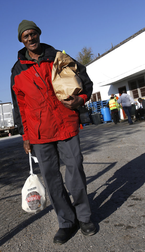 Photo - A man carries his turkey and a sack of groceries from the annex.  Jesus House distributed turkeys and grocery items Tuesday morning,  Nov. 19, 2012. Officials said they had 400 turkeys and food baskets to distribute and people were standing in line when their doors opened at 8 a.m. In less than two yours, all turkeys had been claimed. They will pass out 400 more turkeys and food baskets on Wednesday.  Photo by Jim Beckel, The Oklahoman