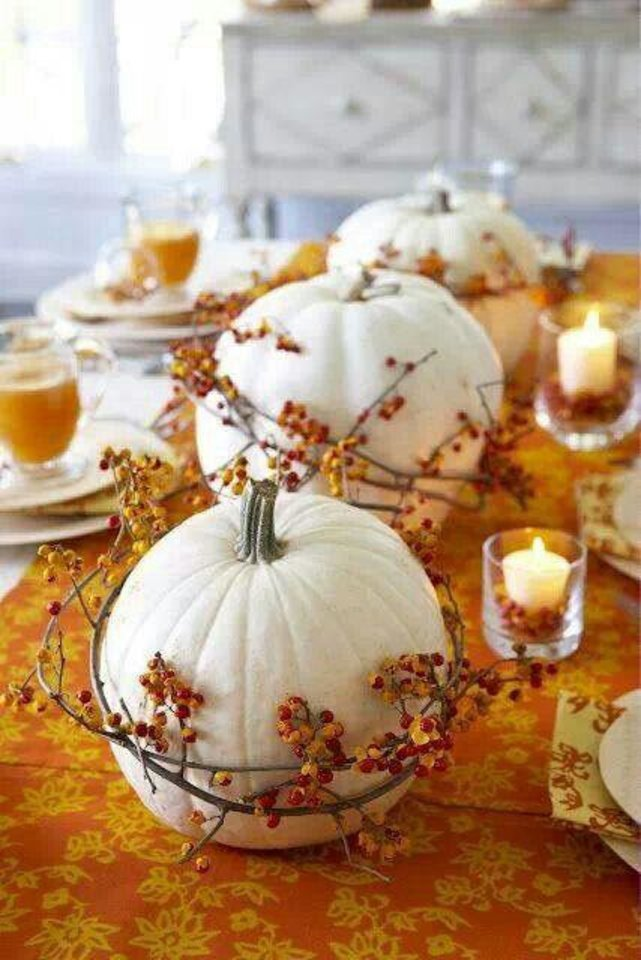 Photo - A beautiful and simple two-toned Thanksgiving color scheme is an elegant way to decorate for a contemporary holiday gathering. This centerpiece of white pumpkins intertwined with gold foliage is tastefully simple yet elegant. From digsdigs.com.