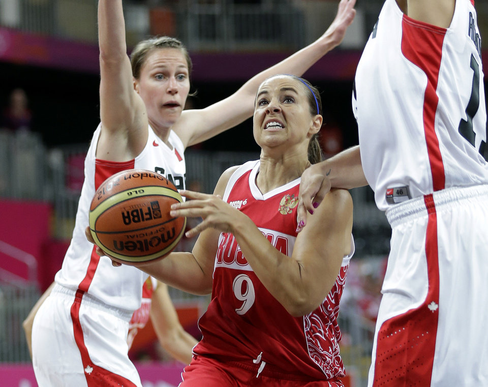 Photo - Russia's Becky Hammon (9) is defended by Canada's Kim Smith, left, and Natalie Achonwa, right, during the first half of a preliminary women's basketball game at the 2012 Summer Olympics, Saturday, July 28, 2012, in London. (AP Photo/Eric Gay)