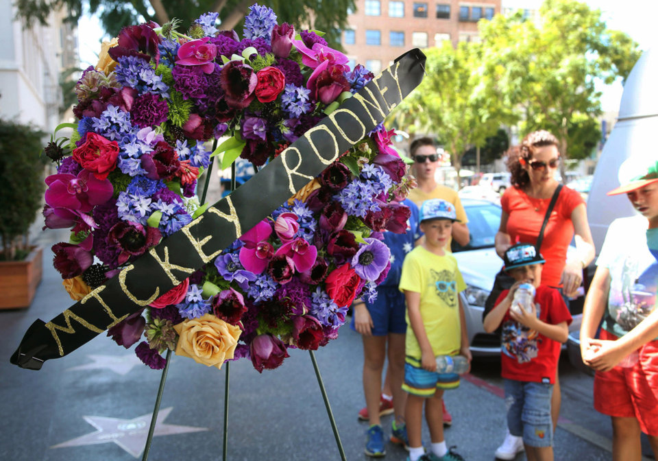 Photo - Tourists from Australia stand by a memorial wreath on the Hollywood Walk of Fame star of Hollywood legend, Mickey Rooney, on Vine Street on Monday, April 7, 2014, in the Hollywood section of Los Angeles. The iconic actor, Rooney, died at 93 on Sunday, April 6, 2014. Over a four-decade span, he was nominated for four Academy Awards, and received two special Oscars for film achievements, won an Emmy for his TV movie
