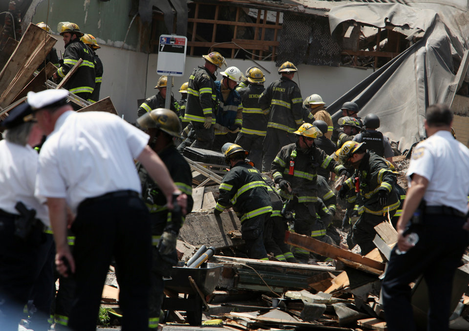 Photo - Rescue personnel search the scene of a building collapse in downtown Philadelphia Wednesday June 5, 2013.  A four-story building being demolished collapsed Wednesday on the edge of downtown, injuring 12 people and trapping two others, the fire commissioner said.  (AP Photo/Jacqueline Larma)