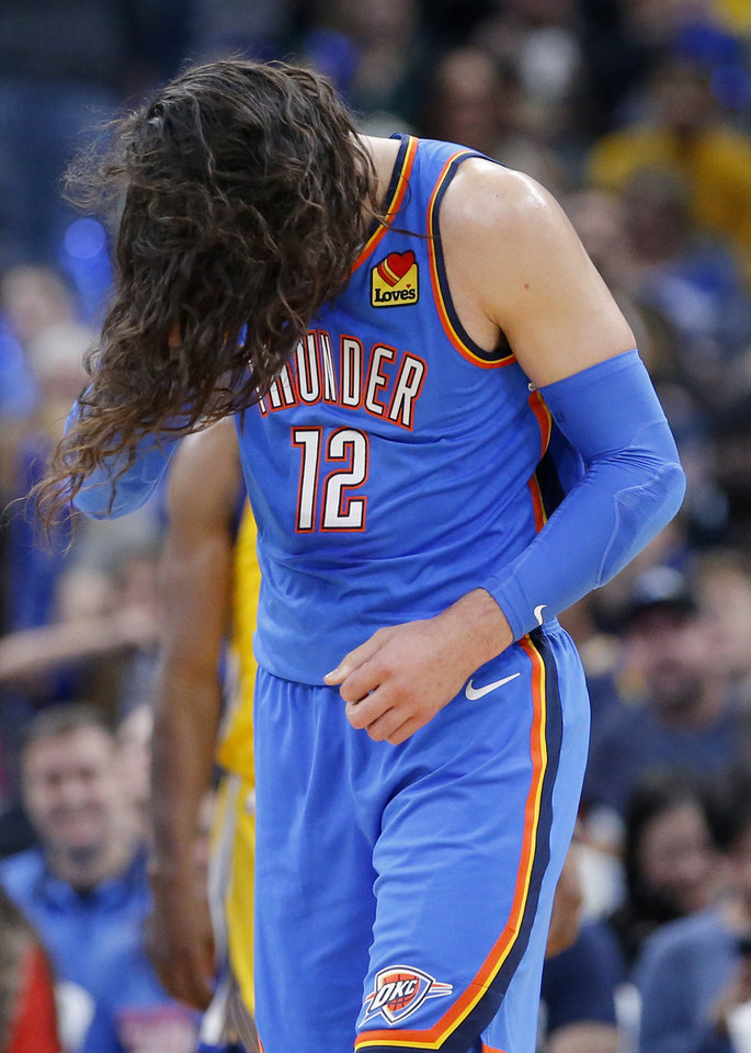 Photo - Oklahoma City's Steven Adams (12) bows his head after his pony tail fell out during the NBA game between the Oklahoma City Thunder and the Golden State Warriors at Chesapeake Energy Arena,   Saturday, Nov. 9, 2019.  [Sarah Phipps/The Oklahoman]