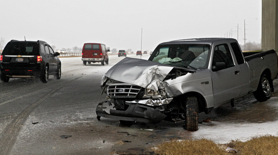Photo - Traffic navigates its way on icy roads past the remains of an injury accident on Lake Hefner Parkway on Thursday Dec. 24, 2009, in Oklahoma City, Okla.   Photo by Chris Landsberger, The Oklahoman