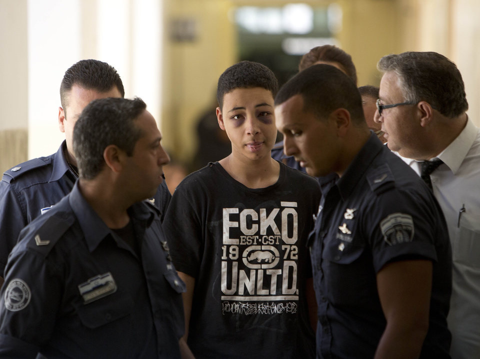 Photo - Tariq Abu Khdeir, 15, a U.S. citizen who relatives say was beaten and arrested by Israeli police during clashes sparked by the killing Thursday of his cousin Mohammed Abu Khdeir, is escorted by Israeli prison guards during an appearance at Jerusalem magistrate's court Sunday, July 6, 2014. Israeli  police said Tariq Abu Khdeir resisted arrest, attacked officers and was carrying a slingshot for lobbing stones when he was arrested. He has been sentenced to nine days of house arrest. The U.S. State Department said it was