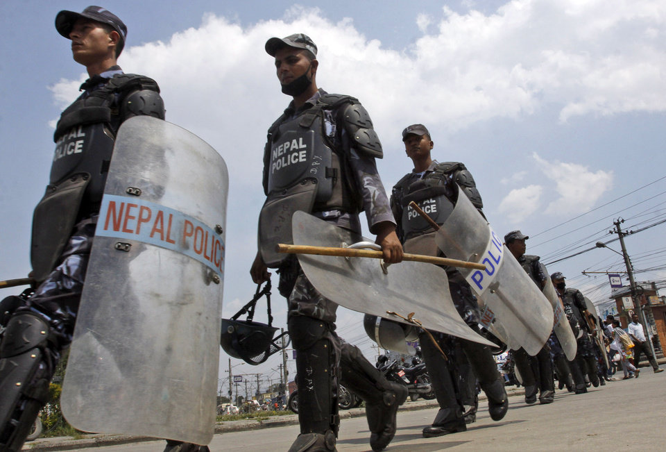 Photo -   Nepalese riot policemen patrol around the venue where leaders of Nepal's major political parties are meeting to form a new coalition government that includes members of the main opposition parties, in Katmandu, Nepal, Thursday, May, 3, 2012. Prime Minister Baburam Bhattarai Bhattarai's press adviser Ram Rijan Yadav said the prime minister will hold talks with leaders of the main political parties later on Thursday to finalize the agreement before making the formal announcement. (AP Photo/Binod Joshi)
