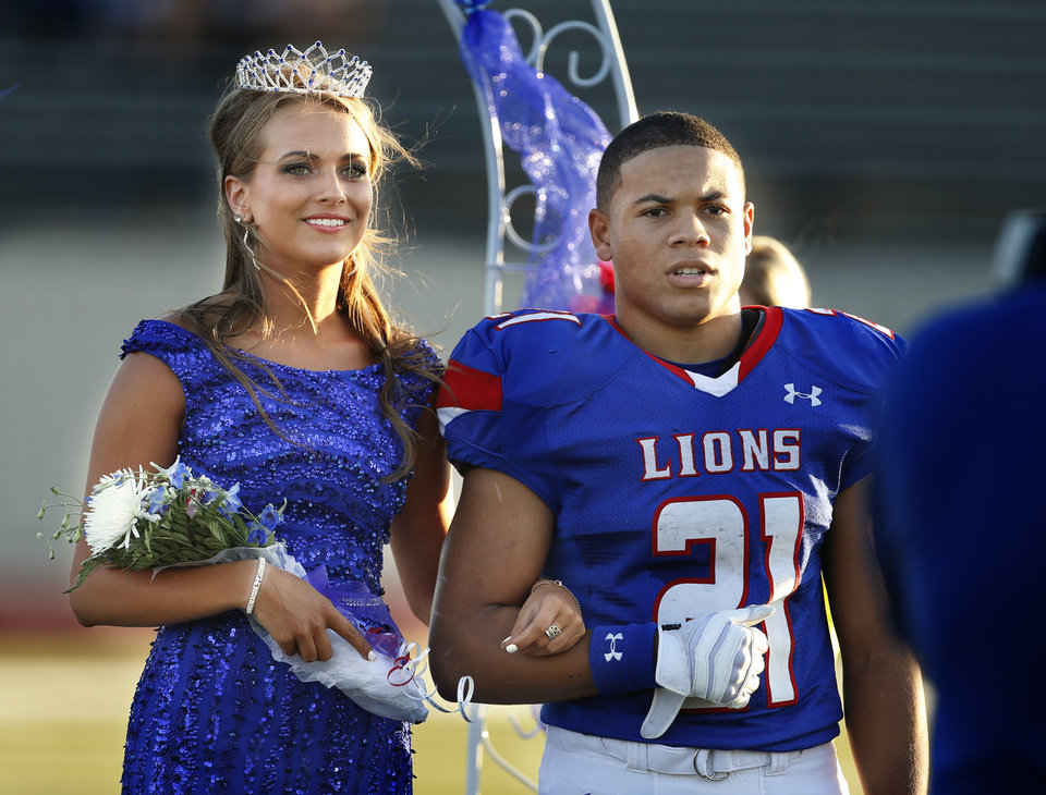 Photo - Moore's Mariah Davis is crowned homecoming queen and is escorted by Ryan Lujan-Leonard as the Moore High School Lions play the Putnam City North Panthers in high school football on Thursday, Oct. 3, 2013, in Moore, Okla.  Photo by Steve Sisney, The Oklahoman