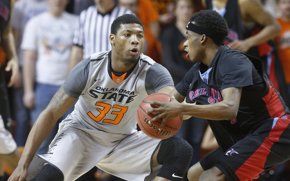 Photo - Delaware State guard Kendal Williams (2) drives as Oklahoma State guard Marcus Smart (33) defends in the second half of an NCAA college basketball game in Stillwater, Okla., Tuesday, Dec. 17, 2013. Oklahoma State won 75-43. (AP Photo/Sue Ogrocki)