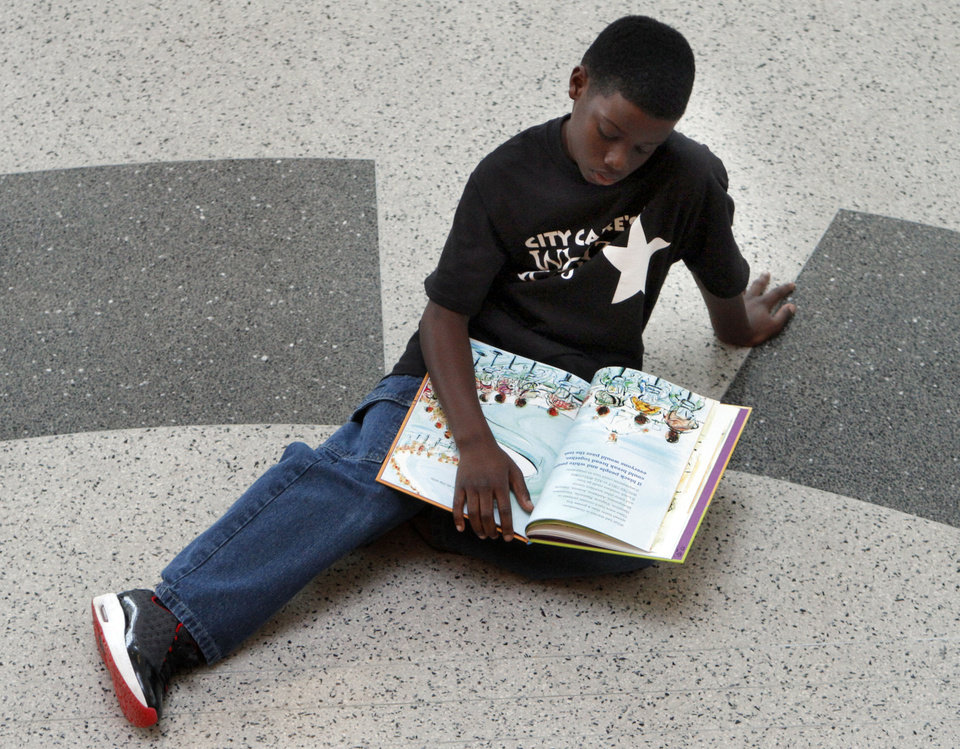 Photo - Carl Albert Middle School student Caleb Collins reads a book before Whiz Kids participants, Carl Albert Middle School students and members of the 2012 Leadership Oklahoma Young Adult Leaders (LOYAL) class, perform a flash mob dance at Ronald J. Norick Downtown LIbrary in Oklahoma City. Photo by Sarah Phipps, The Oklahoman  SARAH PHIPPS