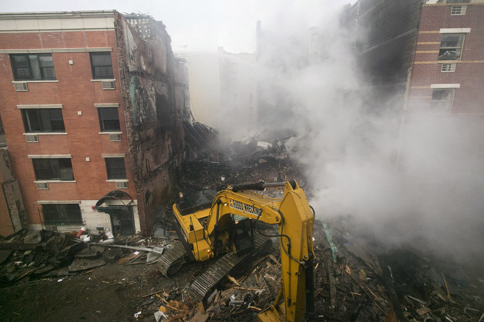 Photo - An excavator works to remove debris from  the site of a building explosion, Thursday, March 13, 2014 in New York. Rescuers working amid gusty winds, cold temperatures and billowing smoke pulled four additional bodies Thursday from the rubble of two New York City apartment buildings, raising the death toll to at least seven from a gas leak-triggered explosion that reduced the area to a pile of smashed bricks, splinters and mangled metal.  The explosion Wednesday morning in East Harlem injured more than 60 people. (AP Photo/Mark Lennihan)