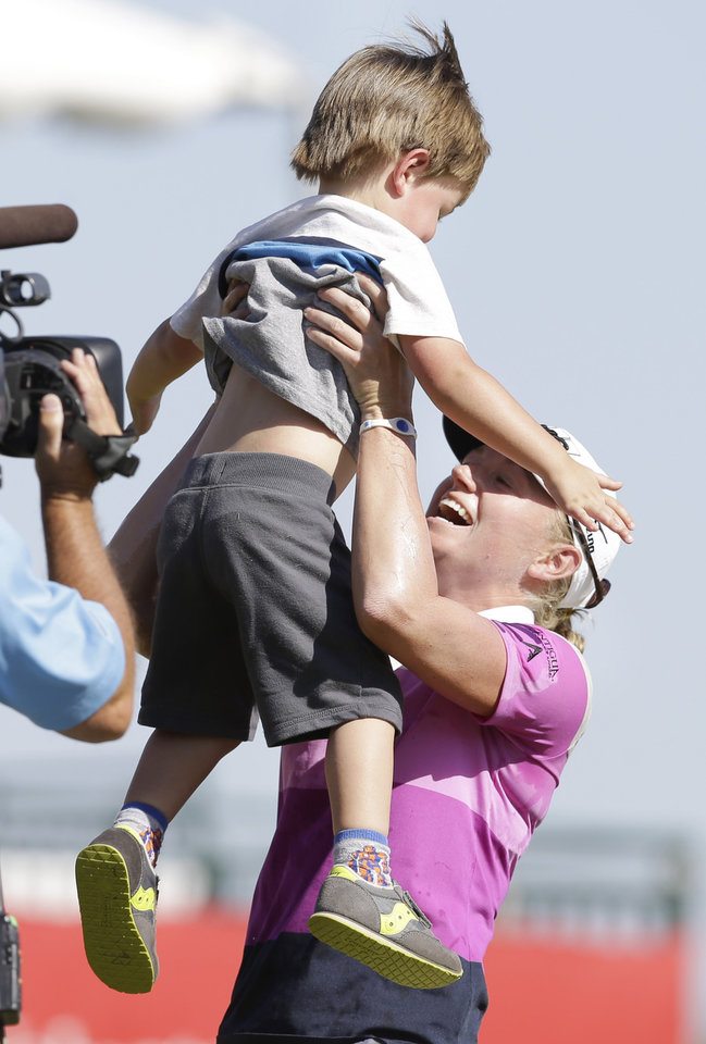 Photo - Stacey Lewis lifts her nephew Cole Wysocki, 3, after winning the North Texas LPGA Shootout golf tournament at Las Colinas Country Club in Irving, Texas, Sunday, May 4, 2014. (AP Photo/LM Otero)