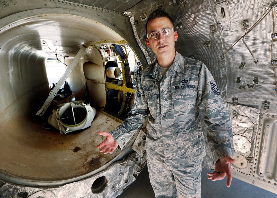 Photo -  Tech. Sgt. Kyle Schulz, with the 76th Expeditionary Depot Maintenance Flight, stands in the shell of a bomber's engine used for training at the APL at Tinker Air Force Base. [Photo by Steve Sisney, The Oklahoman]