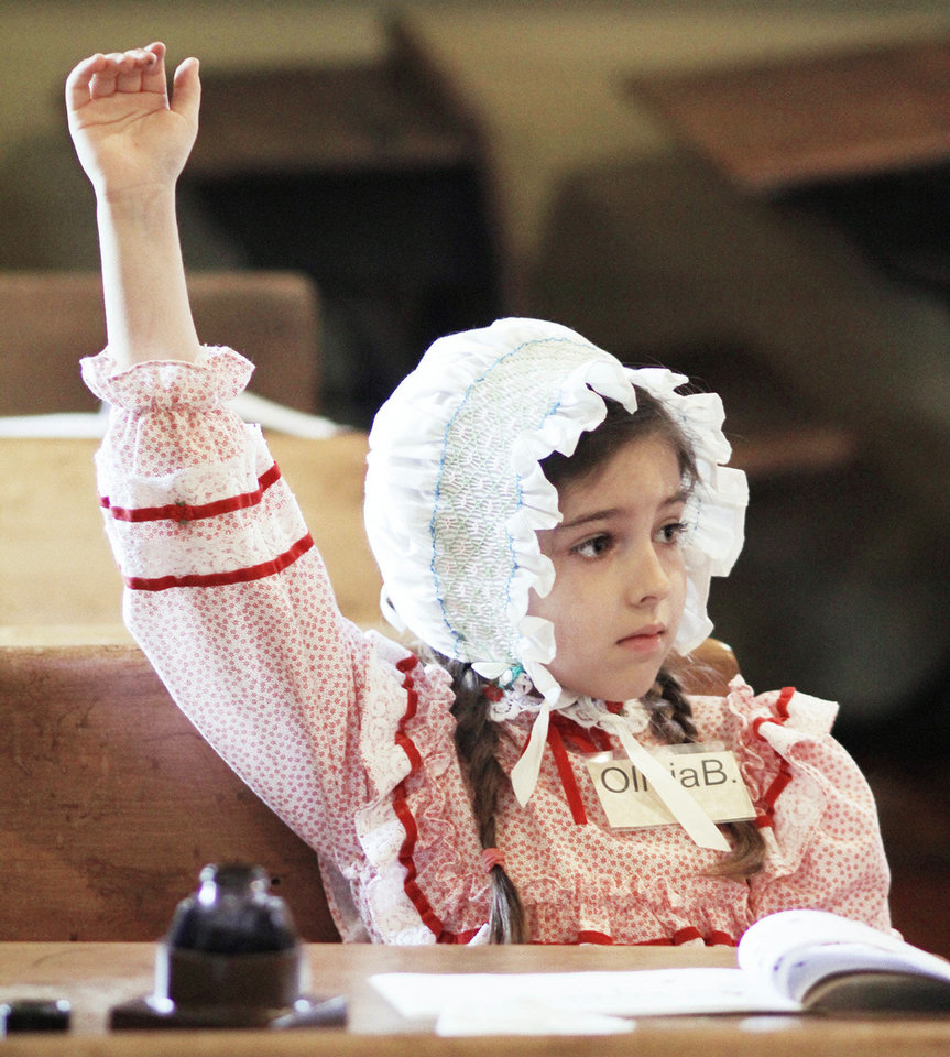 Photo - Above: Olivia Baca, 7, raises her hand to answer a question while attending 1889 Schoolhouse Summer Camp in Edmond, Wednesday.