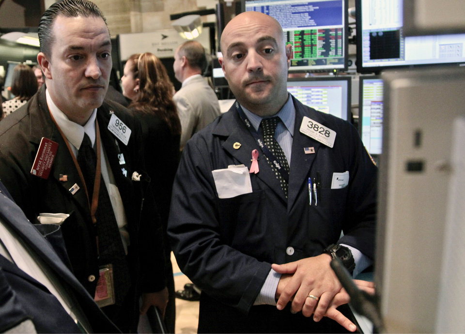 Photo -   FILE - In this June 6, 2012 file photo, Wellington Shields' Theodore Nelson, left, and Knight Capital's Frank Babino, right, work on the floor of the New York Stock Exchange. U.S. stock futures are following markets higher across the globe Monday, June 11, 2012, after the European Union said it would lend Spain as much as $125 billion to save its banks. (AP Photo/Bebeto Matthews, File)