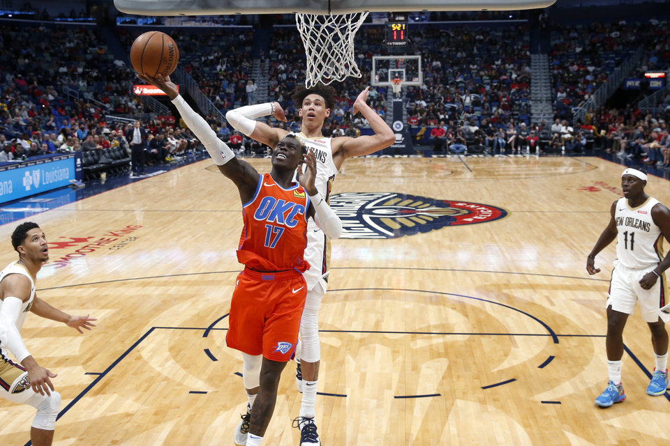 Photo - Oklahoma City Thunder guard Dennis Schroder (17) goes to the basket in front of New Orleans Pelicans center Jaxson Hayes in the second half of an NBA basketball game in New Orleans, Sunday, Dec. 1, 2019. The Thunder won 107-104. (AP Photo/Gerald Herbert)