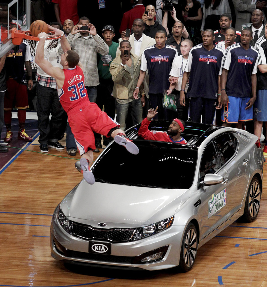 Photo - Los Angeles Clippers' Blake Griffin flies over a car for a dunk after teammate Baron Davis threw him the ball from the sunroof during the Slam Dunk Contest at the NBA basketball All-Star Saturday Night, Saturday, Feb. 19, 2011, in Los Angeles.  (AP Photo/Jae C. Hong)