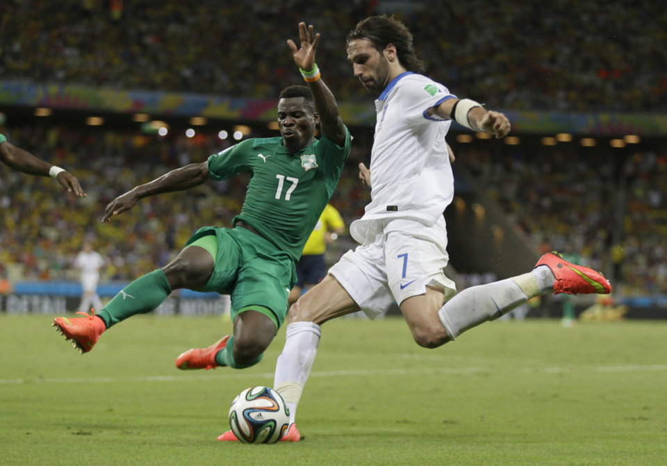 Photo - Ivory Coast's Serge Aurier, left, blocks a shot by Greece's Giorgos Samaras during the group C World Cup soccer match between Greece and Ivory Coast at the Arena Castelao in Fortaleza, Brazil, Tuesday, June 24, 2014. (AP Photo/Natacha Pisarenko)