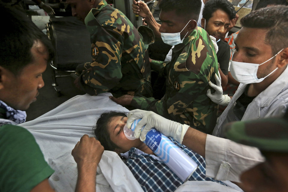 Photo - A Bangladeshi garment worker who was pulled alive from the rubble is wheeled on a stretcher at the site of a building that collapsed Wednesday in Savar, near Dhaka, Bangladesh, Friday, April 26, 2013. The death toll reached hundreds of people as rescuers continued to search for injured and missing, after a huge section of an eight-story building that housed several garment factories splintered into a pile of concrete.(AP Photo/Kevin Frayer)