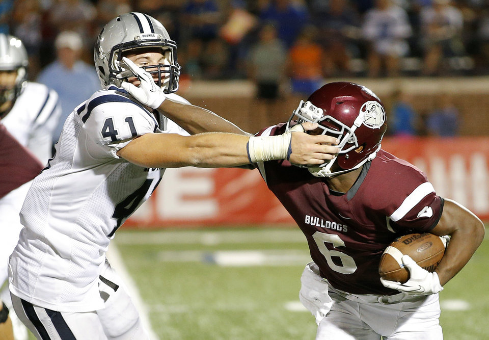 Photo - Edmond Memorial's Warren Wand fights off Edmond North's Scott Courtney during their high school football game at Wantland Stadium in Edmond, Friday, September 6, 2013. Photo by Bryan Terry, The Oklahoman