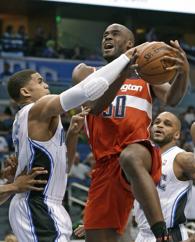 Washington Wizards' Emeka Okafor, center, is fouled by Orlando Magic's Tobias Harris, left, as Magic's Jameer Nelson, right, watches during the first half of an NBA basketball game, Friday, March 29, 2013, in Orlando, Fla. (AP Photo/John Raoux)