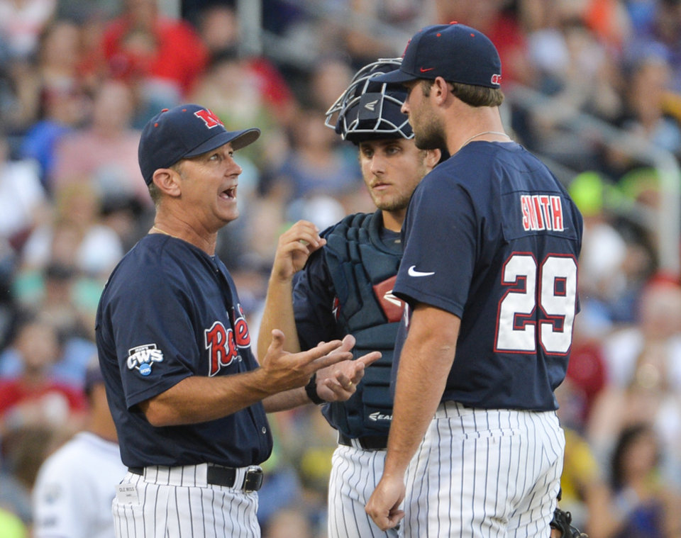 Photo - Mississippi coach Mike Bianco, left, talks to pitcher Sam Smith (29) and catcher Austin Knight, center, in the fourth inning of an NCAA baseball College World Series elimination game against TCU in Omaha, Neb., Thursday, June 19, 2014. (AP Photo/Ted Kirk)