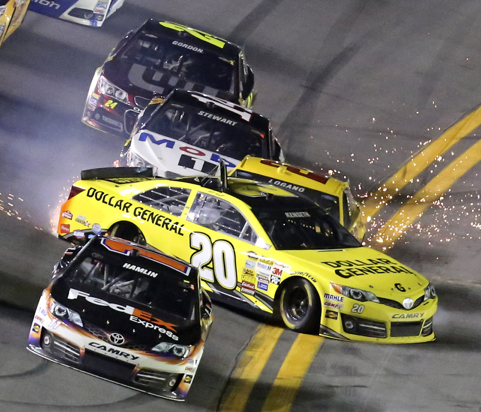 Photo - Matt Kenseth (20) slides sideways in front of Joey Logano (22), Tony Stewart (14) and Jeff Gordon (24), starting a multi-car crash in the front stretch during the NASCAR Sprint Unlimited auto race at Daytona International Speedway in Daytona Beach, Fla., Saturday, Feb. 15, 2014. Denny Hamlin, front, escaped the wreck. (AP Photo/David Graham)