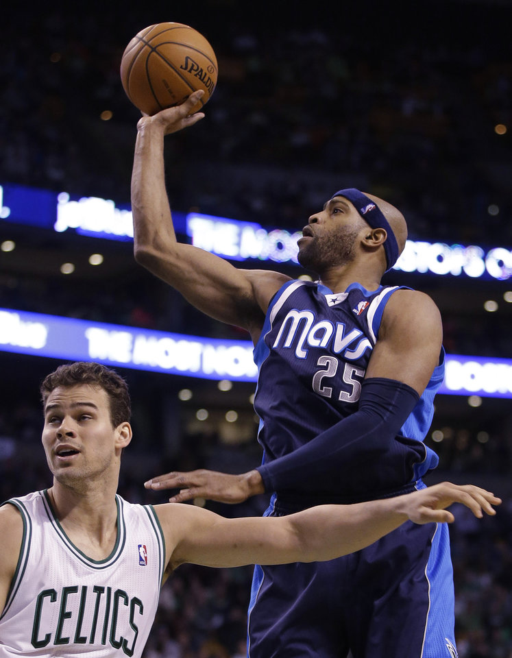 Photo - Dallas Mavericks shooting guard Vince Carter (25) shoots over Boston Celtics center Kris Humphries (43) during the second half of their NBA basketball game in Boston, Sunday, Feb. 9, 2014. The Mavericks defeated the Celtics 102-91. (AP Photo/Stephan Savoia)