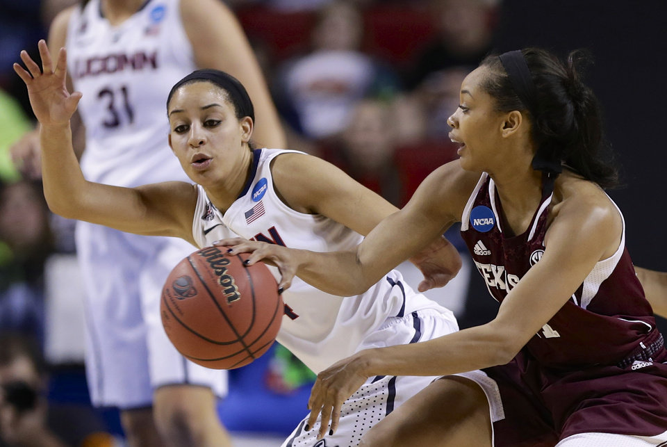 Photo - Texas A&M's Curtyce Knox, right, passes the ball past Connecticut's Bria Hartley, left, during the first half of a regional final game in the NCAA college basketball tournament in Lincoln, Neb., Monday, March 31, 2014. (AP Photo/Nati Harnik)