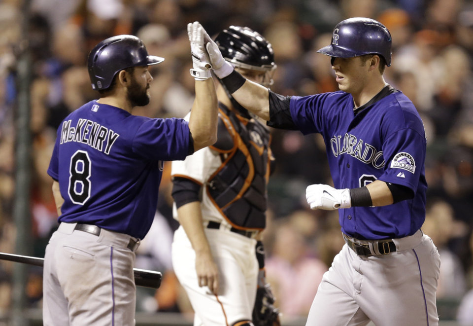 Photo - Colorado Rockies' Corey Dickerson, right, is congratulated by Michael McKenry (8) after Dickerson hit a home run off San Francisco Giants' Tim Hudson in the fifth inning of a baseball game Wednesday, Aug. 27, 2014, in San Francisco. (AP Photo/Ben Margot)