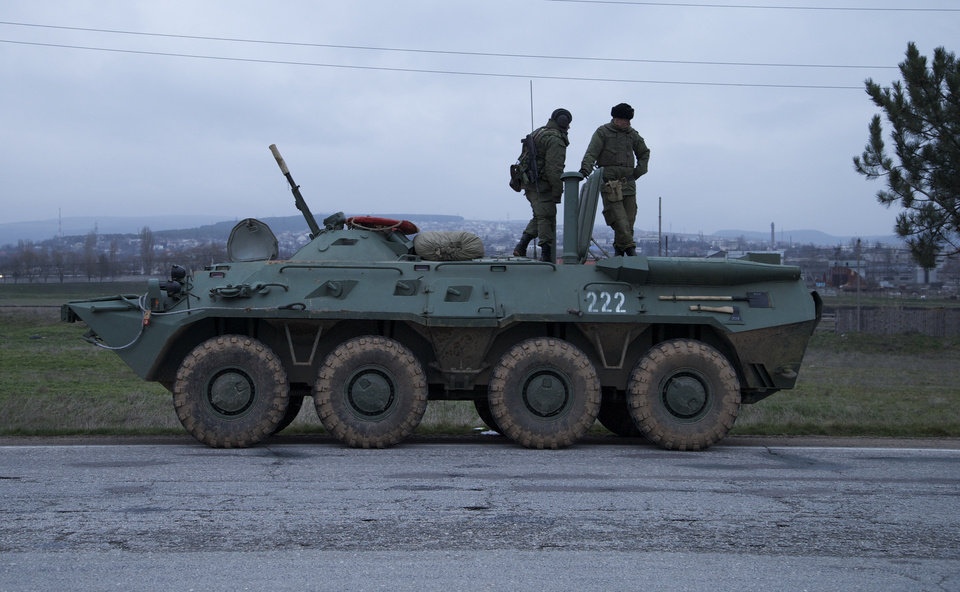 Photo - Soldiers stand atop a Russian armored personnel carrier near the town of Bakhchisarai, Ukraine, Friday, Feb. 28, 2014. The vehicles were parked on the side of the road near the town of Bakhchisarai, apparently because one of them had mechanical problems. (AP Photo/Ivan Sekretarev)