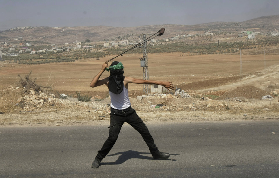 Photo - A Palestinian protester throws a stone towards Israeli soldiers during clashes, following a protest against the Israeli military action in Gaza, in the West Bank city of Nablus on Friday, Aug. 22, 2014. (AP Photo/Nasser Ishtayeh)