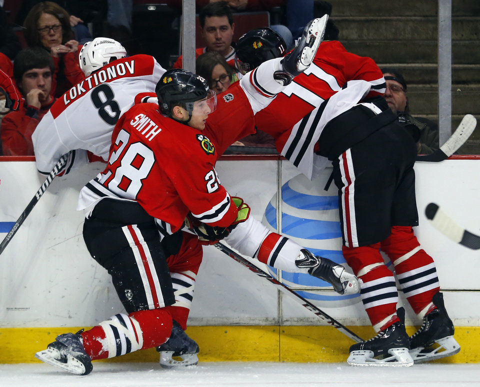 Photo - Carolina Hurricanes center Andrei Loktionov (8) is checked into the boards by Chicago Blackhawks left wing Jeremy Morin (11) and right wing Ben Smith (28) during the second period of an NHL hockey game in Chicago, Friday, March 21, 2014. (AP Photo/Jeff Haynes)