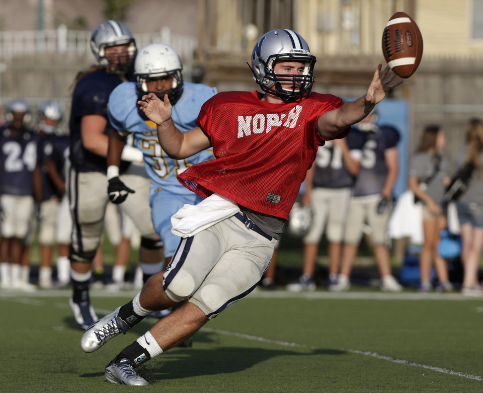 Photo - Edmond North's Stephen McClernon (15) passes a ball during a scrimmage at Putnam City West High School in Bethany, Thursday, Aug. 21, 2014.  Photo by Garett Fisbeck, For The Oklahoman