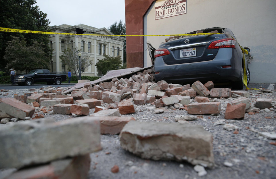Photo - Bricks and fallen rubble cover a car with the old courthouse in the background following an earthquake Sunday, Aug. 24, 2014, in Napa, Calif. A large earthquake rolled through California's northern Bay Area early Sunday, damaging some buildings, igniting fires, knocking out power to tens of thousands and sending residents running out of their homes in the darkness. (AP Photo/Eric Risberg)