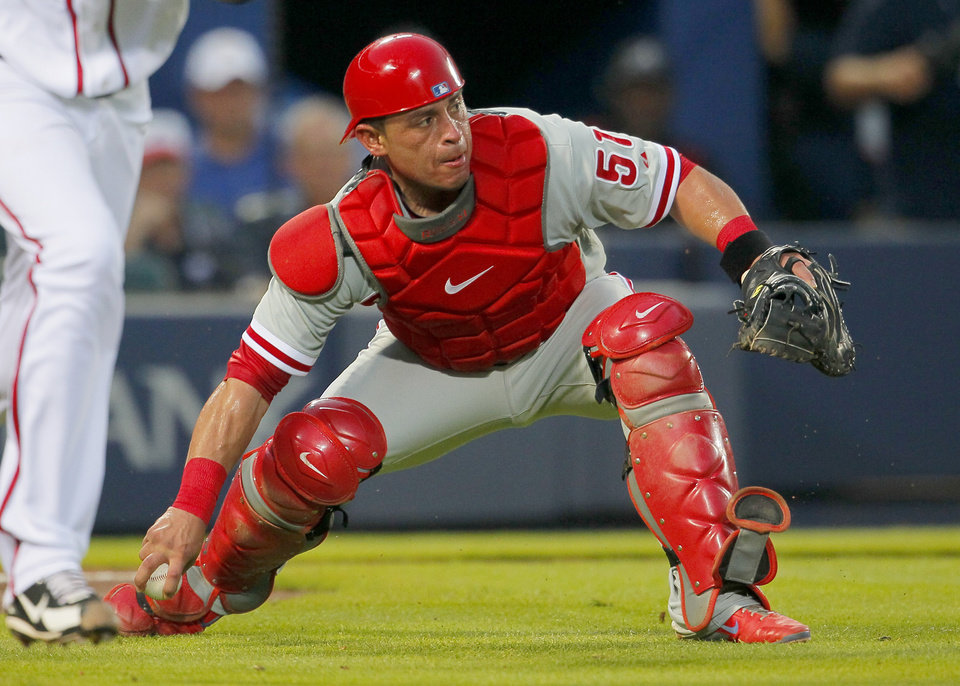 Photo - Philadelphia Phillies catcher Carlos Ruiz (51) fields the bunt from Atlanta Braves Ervin Santana and throws to first for the out in the fifth inning of a baseball game Tuesday, June 17, 2014, in Atlanta. (AP Photo/Todd Kirkland)